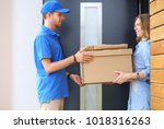 smiling delivery man in blue... | Shutterstock . vector #1018316263