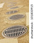 Uneven Line up of Sewer Drains on a sidewalk - stock photo