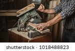 Small photo of Carpenter uses a circular saw on the wooden table
