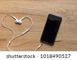 earphones and mobile phone with ... | Shutterstock . vector #1018490527