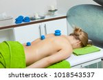 Small photo of Spa relaxation, healthy pleasure, beauty concept. Woman lying on stomach, getting spa therapy cupping glass vacuum massage in salon. Alternative medicine procedure, body care.
