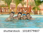 family relaxing  in the pool | Shutterstock . vector #1018579807