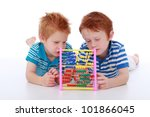 Two red head cheeky boy brothers wearing blue, lying and counting maths with an abacus isolated on white - stock photo