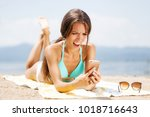 sexy girl on a beach with... | Shutterstock . vector #1018716643