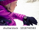 Small photo of Woman hiker checking the elevation on sports watch, smartwatch with altimeter app in winter woods and mountains. Female trekker in white snowy forest trekking with electronics equipment technology.