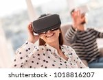 Small photo of Technological advance. Cheerful gay attractive woman smiling while tuning VR glasses and looking up