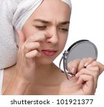 Close-up of teenager finding an acne on her nose wit towel on her head - stock photo