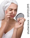 Woman finding an acne on her nose wit towel on her head - stock photo