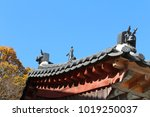 Small photo of Korean traditional architecture detail of roof with bestial face sculpture at Beomeosa Temple in Busan, South Korea