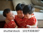 Small photo of Happy chinese new year. 3 cute asian little boys are playing together. There are Chinese blessing words Longevity, auspicious and wealthy in the Chinese suit.