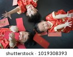 Small photo of Happy chinese new year. 3 cute asian little boys are playing red envelopes together on the bed. There are Chinese blessing words Longevity, auspicious and wealthy in the Chinese suit.