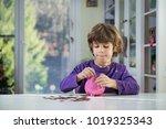 little boy putting coins into... | Shutterstock . vector #1019325343