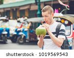 young man drinking coconut... | Shutterstock . vector #1019569543