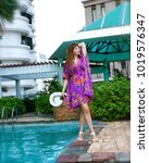 Small photo of blue-eyed, long haired girl in a short coloured Indian tunica is posing near the swimming pool