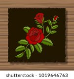 Stock vector embroidery roses and sprigs on a dark flap cloth and wooden texture background floral ornament 1019646763