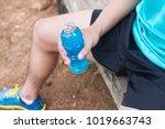 bottle of energy drink in hands ... | Shutterstock . vector #1019663743