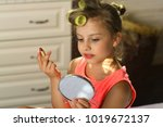 Stock photo little girl with curlers wears fashionable dress indoors beauty and kids makeup concept kid with 1019672137