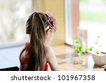 Little child girl sitting at a table facing away from the camera - stock photo