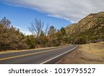 a highway disappearing around a ... | Shutterstock . vector #1019795527