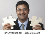 Happy East Indian Businessman holding puzzle pieces - stock photo