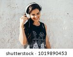 young woman listening to music... | Shutterstock . vector #1019890453