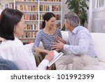 couple arguing during therapy session with psychologist - stock photo
