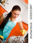 Attractive brunette woman cleaning kitchen using dish washing machine. - stock photo