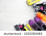 Small photo of Gym stuff, mobile phone and blank space for exercise plan on wooden background. Flat lay composition
