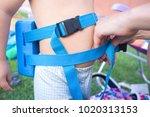 mom adjusting the float belt of ... | Shutterstock . vector #1020313153