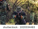Small photo of Soldiers holding rifles ambushed, tree