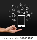 Hand holding smartphone, lots of gadgets at your finger tips. - stock photo