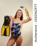 Small photo of Attractive slim woman wearing swimsuit with mask tuba, flippers, snorkel having fun studio shot on grey. Young female dreaming about summer vacation. Snorkeling swimming concept