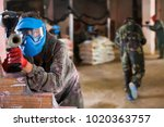 Small photo of Player in blue mask is targeting in adversary in battlefield in paintball club.
