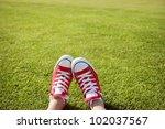 feet in sneakers in green grass | Shutterstock . vector #102037567