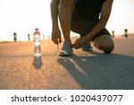 male runner tying shoes in... | Shutterstock . vector #1020437077