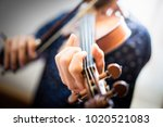 a young man is playing a violin ... | Shutterstock . vector #1020521083