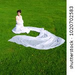Small photo of Oriental girl sits on green grass in a white shroud