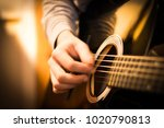 Small photo of Hand strumming the strings of a black acoustic steel string guitar with warm reflections on the body