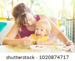 mom feed cute young child | Shutterstock . vector #1020874717