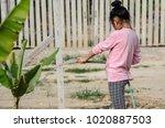 asian girl watering banana tree ...   Shutterstock . vector #1020887503