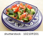A moroccan salad of tomato, cucumber, onion and coriander (cilantro) leaves tossed in olive oil and vinegar and finished with lemon juice - stock photo