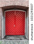 Small photo of double red door placed in an alcove of an old wall