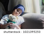 Small photo of Patient kid lie down on couch or sofa in patient suit with her doll.Girl cover her head with blue hat or headscarf.Kid look sad,tired and sick.Concept of childhood cancer awareness.Selective focus.