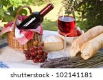 Romantic lunch setting with wine, bread and fruit - stock photo