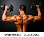 rear view of bodybuilder training with dumbbells on black background - stock photo