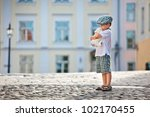 Cute little boy sitting on father's shoulders outdoors in city park - stock photo