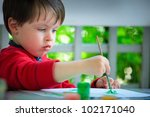 Cute three years old boy painting with brush - stock photo