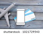 Small photo of plane, tickets, smartphone with a white screen on a wooden background. journey. tourism. air transportation.