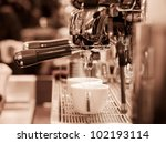 prepares espresso in his coffee shop; close-up  monotone - stock photo