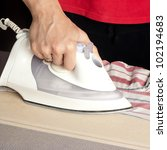 close up of  ironing laundry on ironing board - stock photo